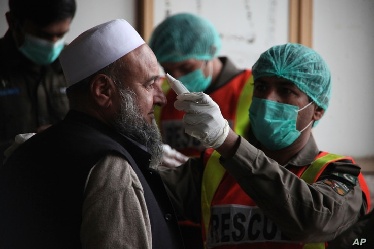 A health official of an emergency rescue service checks the body temperature of a government employee in Peshawar, Pakistan,…