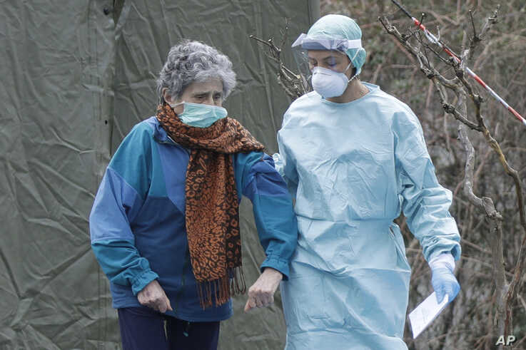 An elderly patient is helped by a doctor at one of the emergency structures that were set up to ease procedures at the Brescia hospital, northern Italy, Thursday, March 12, 2020.