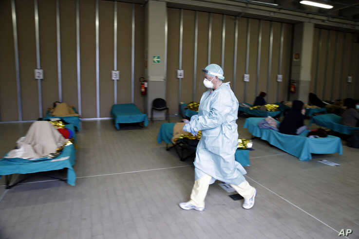 Patients lie on beds as a doctor walks past them, at a one of the emergency structures that were set up to ease procedures at the Brescia hospital, northern Italy, March 12, 2020.