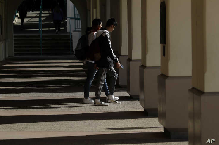 Students walk on the San Diego State University campus Thursday, March 12, 2020, in San Diego.