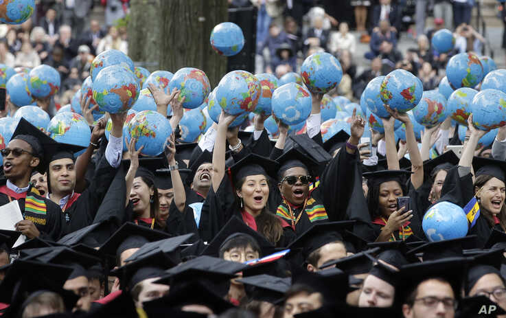 FILE - In this May 30, 2019, file photo, graduates of Harvard's John F. Kennedy School of Government hold aloft inflatable…