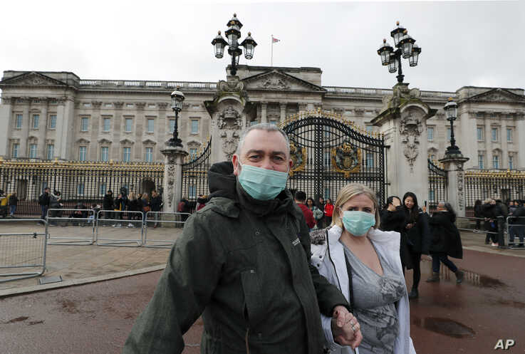 A couple wear face masks as they visit Buckingham Palace in London, Saturday, March 14, 2020.