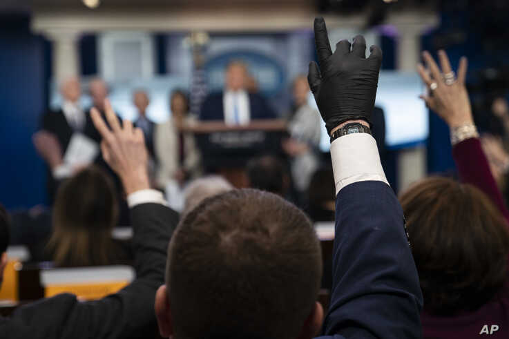 Reporters raise their hands to ask President Donald Trump questions during a press briefing with the coronavirus task force, at…