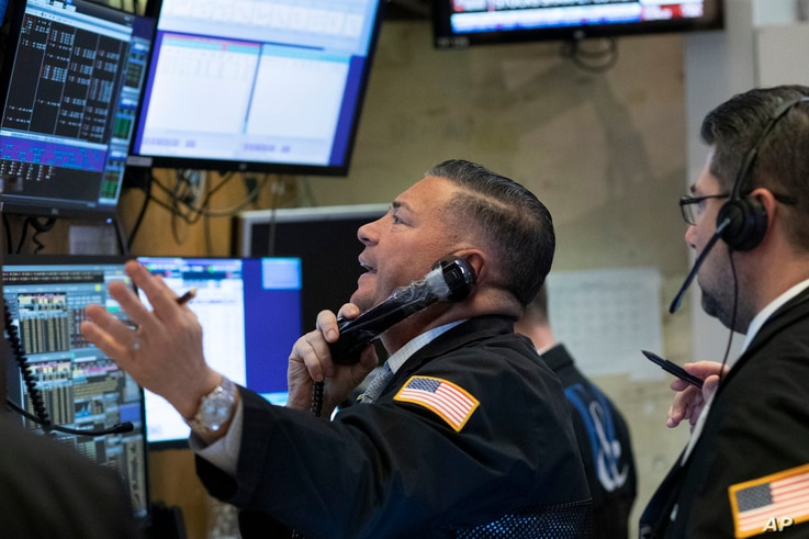 Traders work at the New York Stock Exchange as the market closes, Wednesday, March 18, 2020 in New York.  Major U.S. stock…
