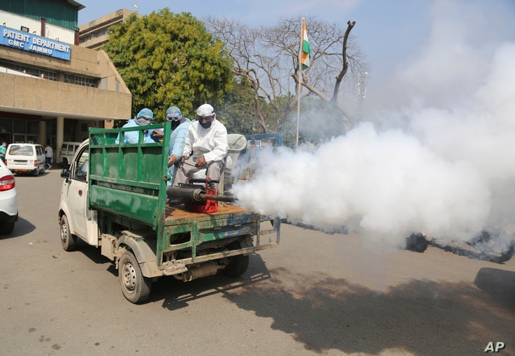 Indian municipal workers spray disinfectants as a precautionary measure against COVID-19 outside Government Medical College…
