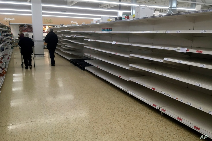 Shoppers walk past empty shelves in a supermarket in Rugby, England, Thursday, March 19, 2020. Supermarkets are limiting the…