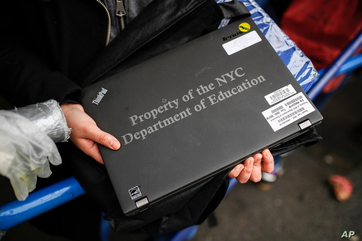Anna Louisa, 18, receives her school laptop for home study at the Lower East Side Preparatory School Thursday, March 19, 2020, in New York, as coronavirus restrictions shuttered classrooms throughout the city.