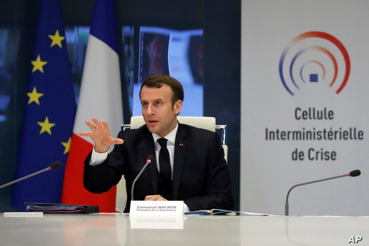 French President Emmanuel Macron attends a meeting at the emergency crisis center of the Interior Ministry in Paris, Friday,…
