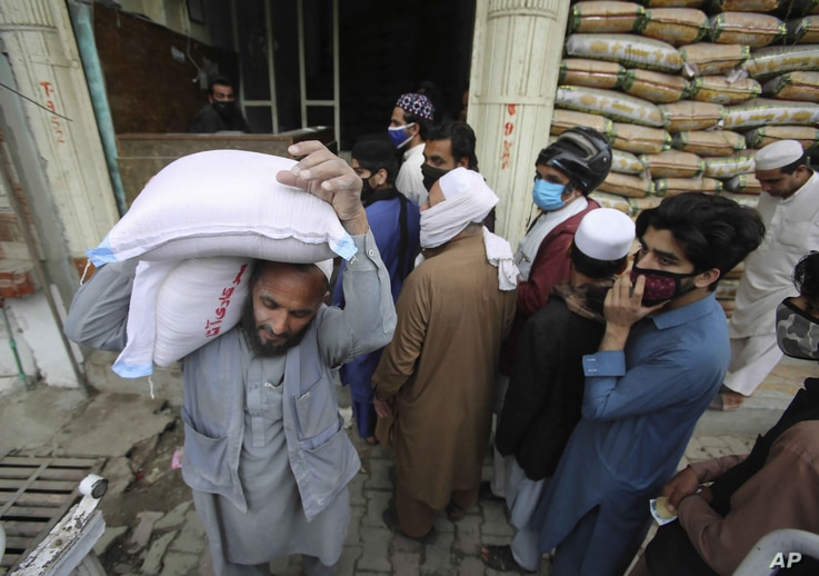 People buy sacks of flour fearing a shortage due to the coronavirus outbreak, in Peshawar, Pakistan, Tuesday, March 24, 2020…