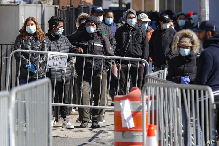 Patients wearing face masks and personal protective equipment wait on line for COVID-19 testing outside Elmhurst Hospital…
