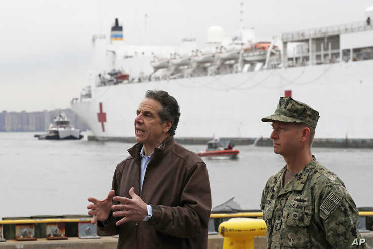 New York Go. Andrew Cuomo, left, speaks as he stands beside Rear Adm. John B. Mustin after the arrival of the USNS Comfort, a…