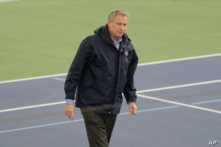 New York City Mayor Bill de Blasio, center, walks the practice courts with officials at the USTA Indoor Training Center where a…