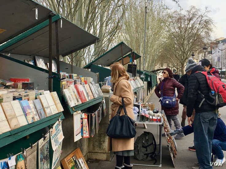 People look at goods being sold at the iconic kiosks by the Seine River in Paris. (Lisa Bryant/VOA)