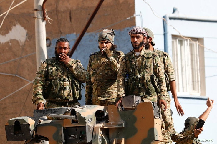 Members of Syrian National Army, known as Free Syrian Army, stand on top of an armored vehicle in the Turkish border town of…