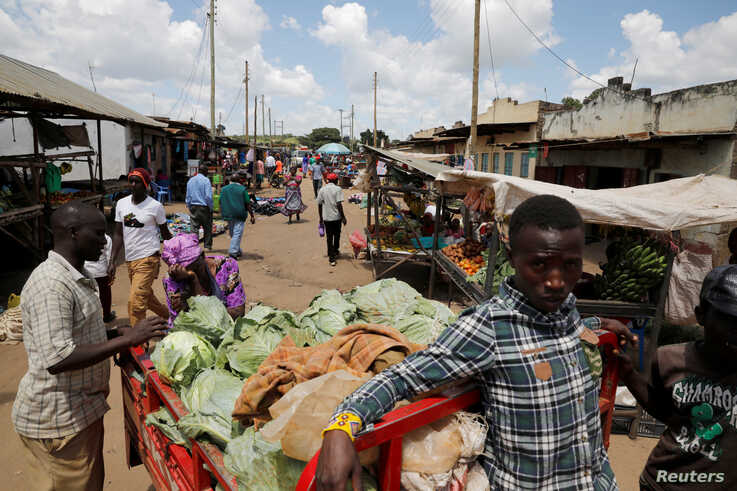 Vendors look at cabbage stored on the back of a tricycle, as it is  brought to the market to be sold in the town of Kiu, south…