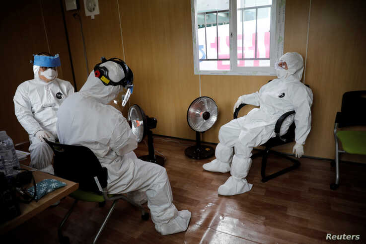 Medical staff in protective gear take a break at a facility of a 'drive-thru' testing center for the novel coronavirus disease of COVID-19 in Yeungnam University Medical Center in Daegu, South Korea, March 3, 2020.