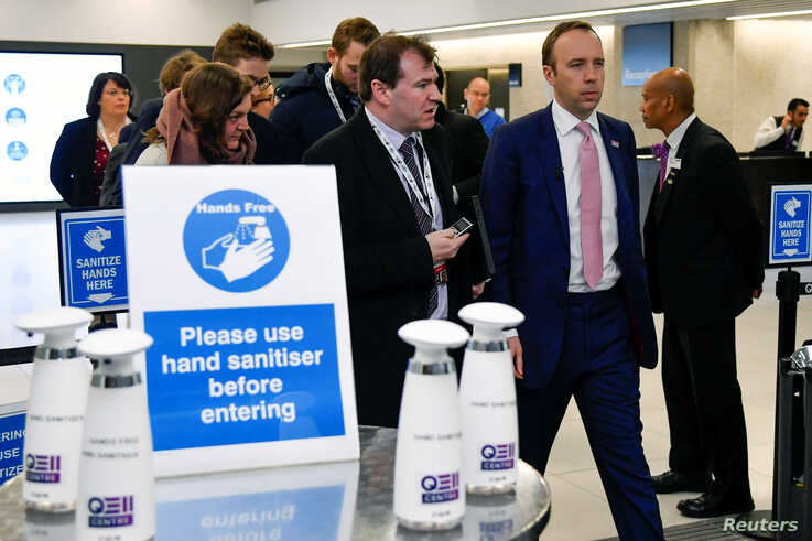 Britain's Health Secretary Matt Hancock walks past a hand sanitising station as he leaves after talking about coronavirus at…