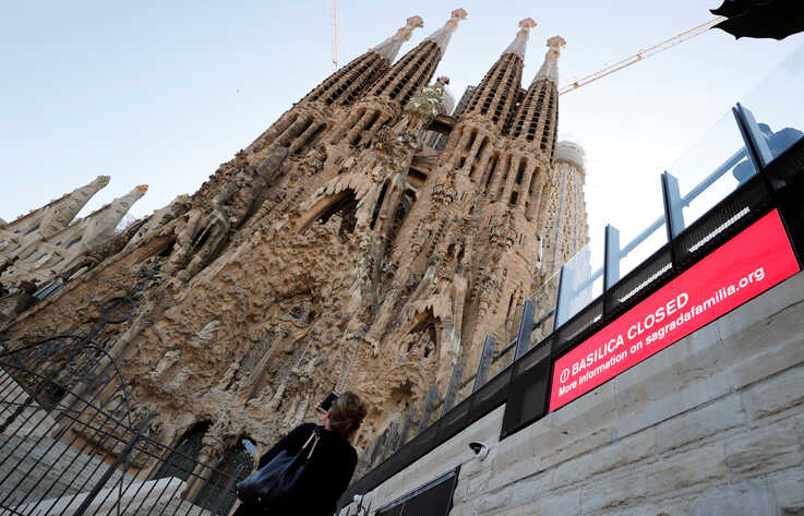 A tourist records with her mobile phone the landmark Sagrada Familia basilica, which stopped receiving visitors and suspend its…