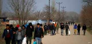Migrants walk in Edirne at the Turkish-Greek border, Monday, March 9, 2020. Thousands of migrants have massed at Turkey's land…