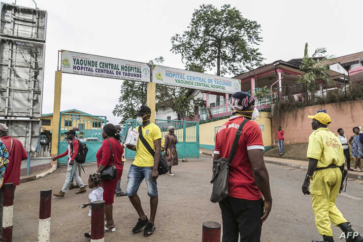 Some people wear masks as they walk by the entrance to the Yaounde General Hospital in Yaounde, March 6, 2020 as Cameroon has confirmed its first case of the COVID-19 coronavirus.