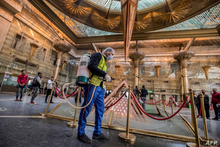 A worker sprays disinfectant at Ramses railway station in Cairo, Egypt, March 20, 2020, as part of a efforts to fight the spread of the coronavirus.