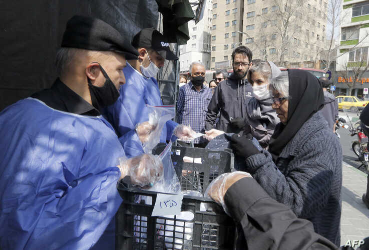 People queue in line to receive packages for precautions against COVID-19 coronavirus disease provided by the Basij, a militia loyal to Iran's Islamic republic establishment, from a booth outside Meydane Valiasr metro station in Tehran, March 15, 2020.