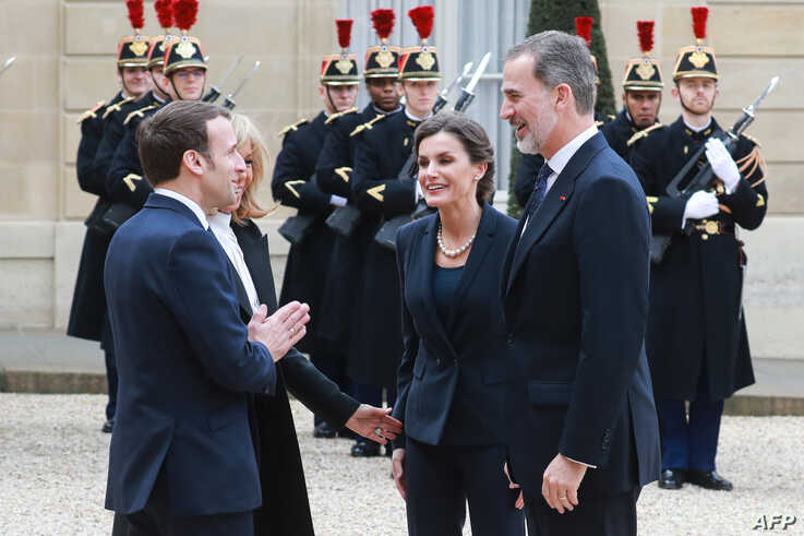 """FILE - France's President Emmanuel Macron (L), with his wife Brigitte Macron by his side, welcomes King Felipe VI (R) and Queen Letizia of Spain (2nd R) with what appears to be a """"namaste"""" greeting, at the Elysee Palace in Paris, France, March 11, 2020."""