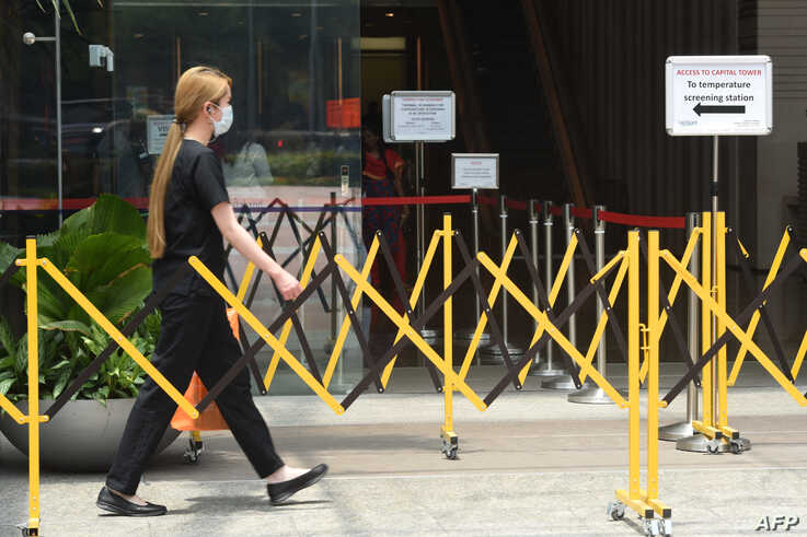 A woman wearing a face mask approaches a temperature screening area of an office building as a preventive measure against the coronavirus spread, in Singapore, March 20, 2020.