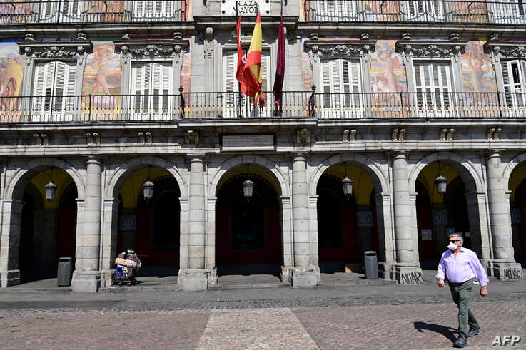 A man wearing a protective face mask walks at the usually crowded Plaza Mayor in central Madrid, Spain, March 14, 2020, after authorities ordered all shops in the region be shuttered die to the coronavirus.