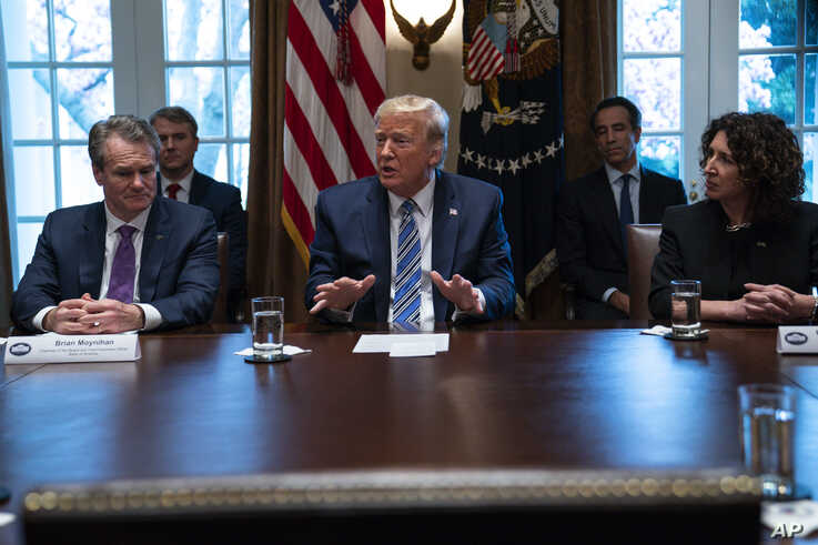 Bank CEOs Brian Moynihan (L) and Rebeca Romero Rainey (R) listen as President Donald Trump speaks during a meeting with banking industry executives about the coronavirus, at the White House, March 11, 2020, in Washington.