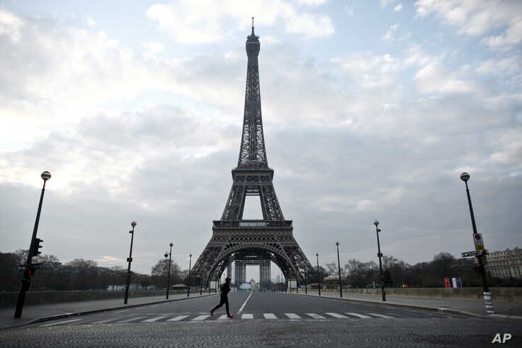 A man runs in front of the Eiffel Tower, in Paris, March 18, 2020.