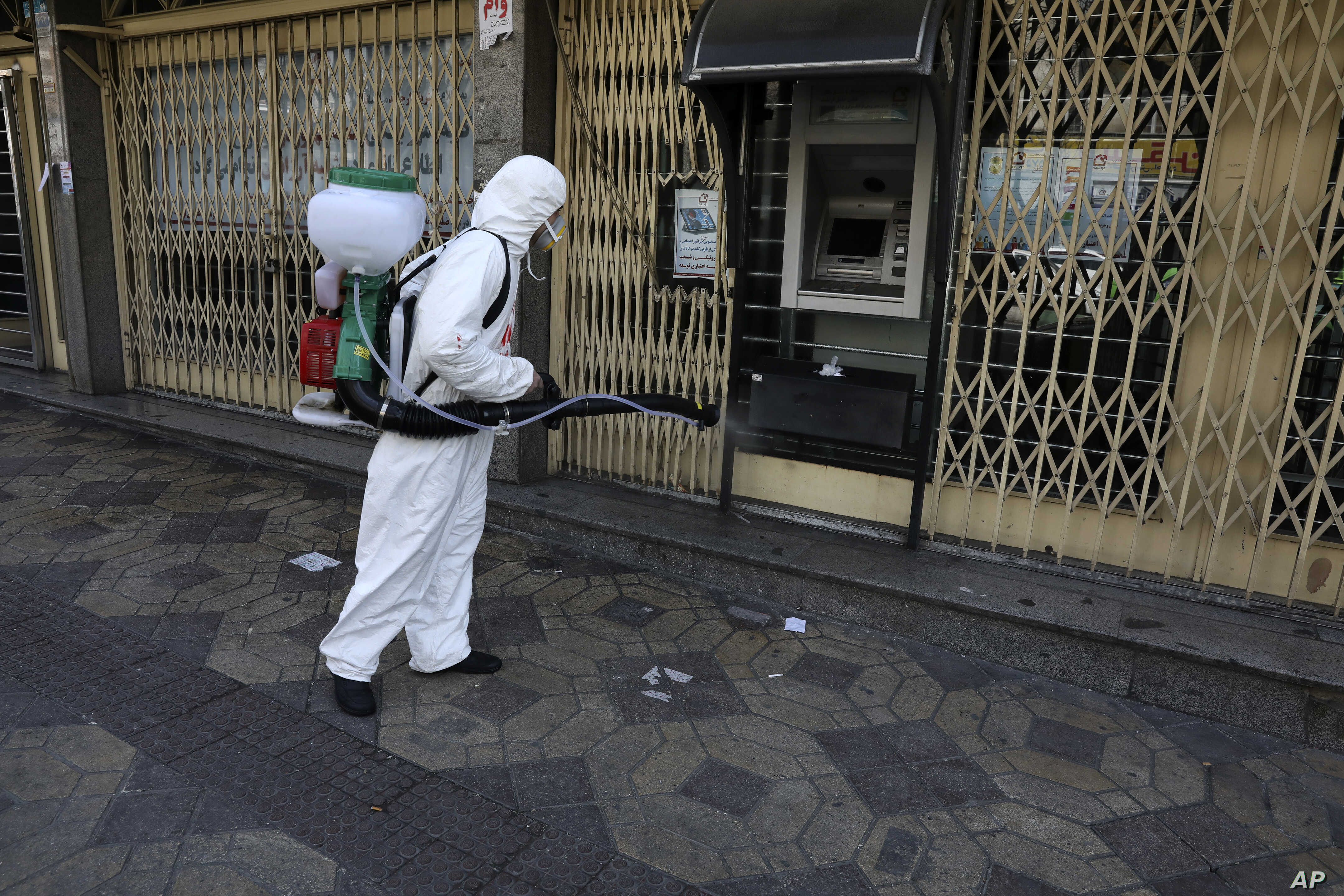 A firefighter disinfects an ATM machine to help prevent the spread of the new coronavirus in Tehran, Iran, March 5, 2020.