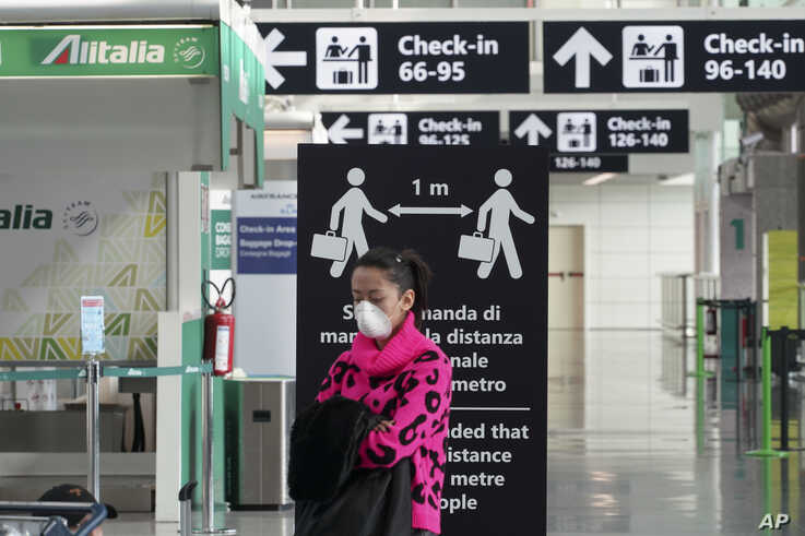 A woman wearing a protective mask stands in front of a notice recommending to keep the social distance of 1 meter between people, at the Leonardo da Vinci international airport, in Rome, March 12, 2020.