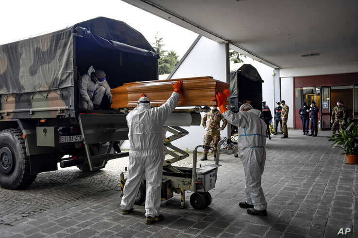 Coffins arriving from the Bergamo area, where the coronavirus infections caused many victims, are being unloaded from a military truck that transported them in the cemetery of Cinisello Balsamo, near Milan in Northern Italy, March 27, 2020.
