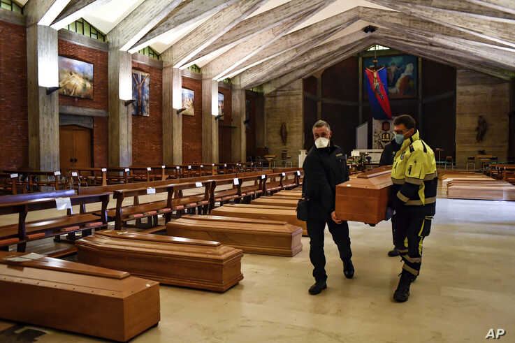 A coffin is carried in the San Giuseppe church in Seriate, one of the areas worst hit by coronavirus, near Bergamo, Italy, waiting to be taken to a crematory, March 26, 2020.