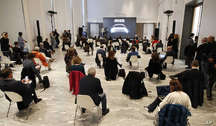 People sit a recommended distance apart from each other during the presentation of the new FIAT 500 electric n Milan, Italy.