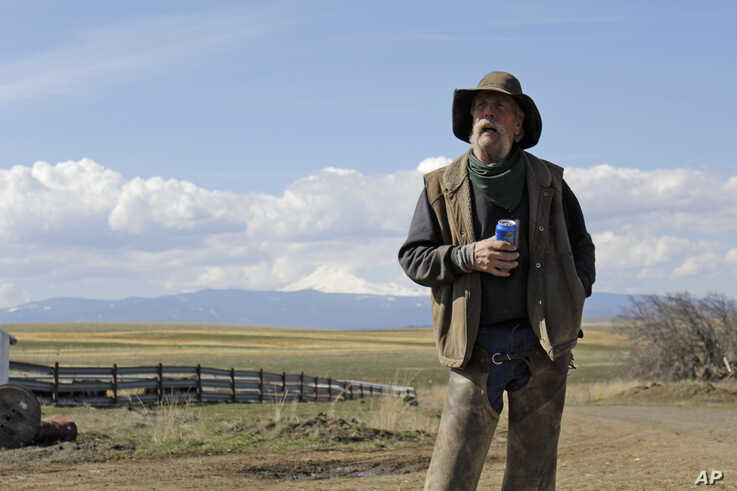 In this photo taken March 20, 2020, cattle rancher Mike Filbin stands on his property in Dufur, Oregon, after herding some cows, and talks about the impact the coronavirus is having on his rural community.