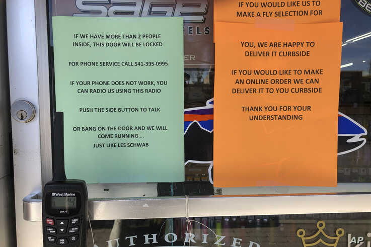 In this photo taken March 20, 2020, a sign outside a fly fishing shop in Maupin, Oregon, advises customers of new policies to limit the spread of the coronavirus in rural areas.