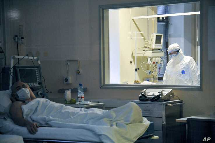 A doctor observes through a glass window the condition of the patient in a ward in the Moscow Sklifosovsky emergency hospital in Moscow, Russia, March 25, 2020.