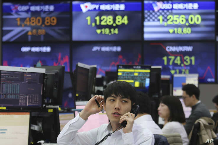 FILE - A currency trader talks on the phone at the foreign exchange dealing room of the KEB Hana Bank headquarters in Seoul, South Korea, March 25, 2020.