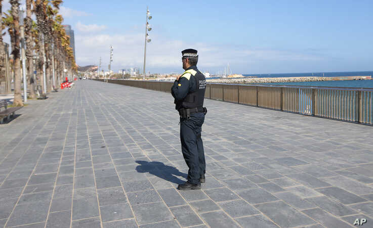 A police officer stands guard preventing access to the beach in Barcelona, Spain, March 15, 2020.