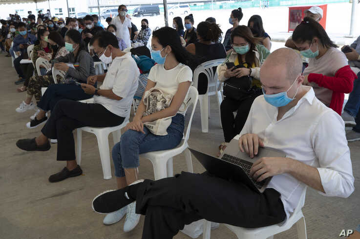 Tourists practice social distancing as they wait to extend their visa at Immigration Bureau in Bangkok, Thailand, March 27, 2020.