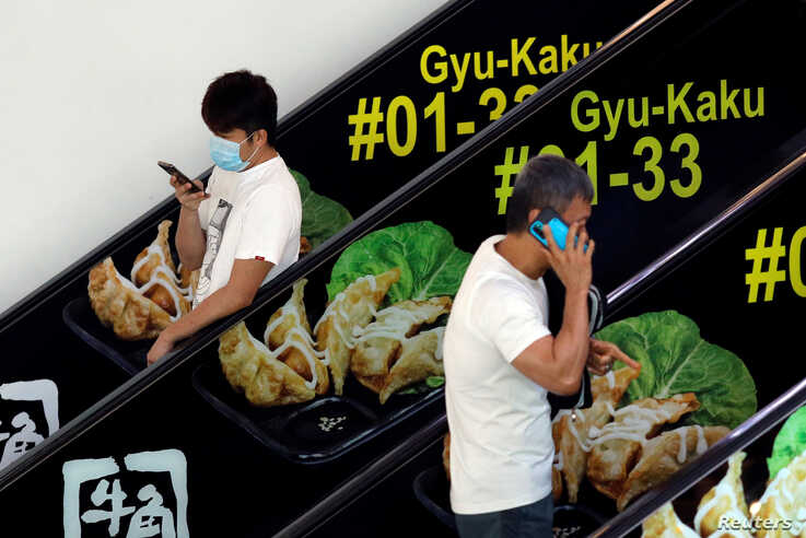 Men, one with a protective mask, use their phones at a mall in Singapore, March 27, 2020.