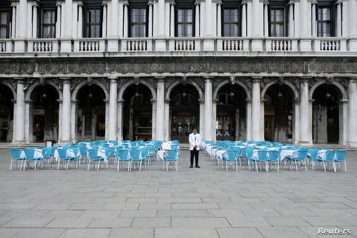 A waiter stands by empty tables outside a restaurant at St Mark's Square, which is usually full of tourists, after Italy's government adopted a decree with new emergency measures to contain the coronavirus, in Venice, Italy, March 5, 2020.