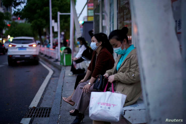 Women wearing face masks wait for buses at a bus stop in Xianning of Hubei province, the epicentre of China's coronavirus disease (COVID-19) outbreak, March 25, 2020.