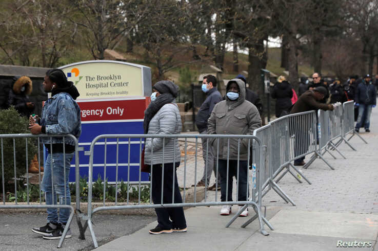 People queue to enter a tent erected to test for the coronavirus disease (COVID-19) at the Brooklyn Hospital Center in Brooklyn, New York City, March 19, 2020.