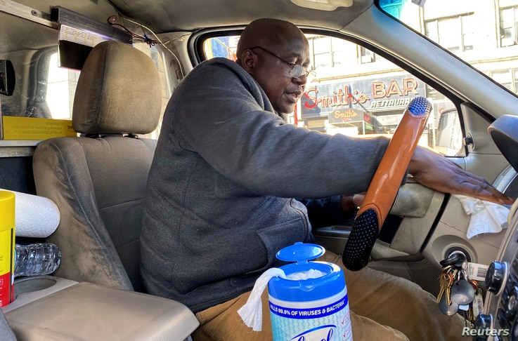Yellow taxi cab driver Martin Oseseyi cleans his cab with disinfectant wipes amid the coronavirus outbreak in midtown Manhattan in New York City, March 4, 2020.