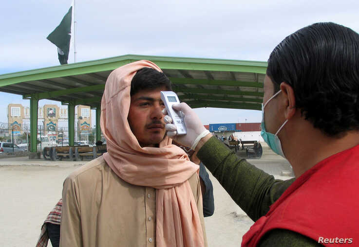 A healtaA health worker takes the temperature of a man, who returned from Afghanistan, following the coronavirus outbreak, outside a medical camp near the Friendship Gate, at the Pakistan-Afghanistan border town of Chaman, Pakistan, Feb. 26. 2020.h worker takes the temperature of a man, who returned from Afghanistan, for a medical observation as a preventive…