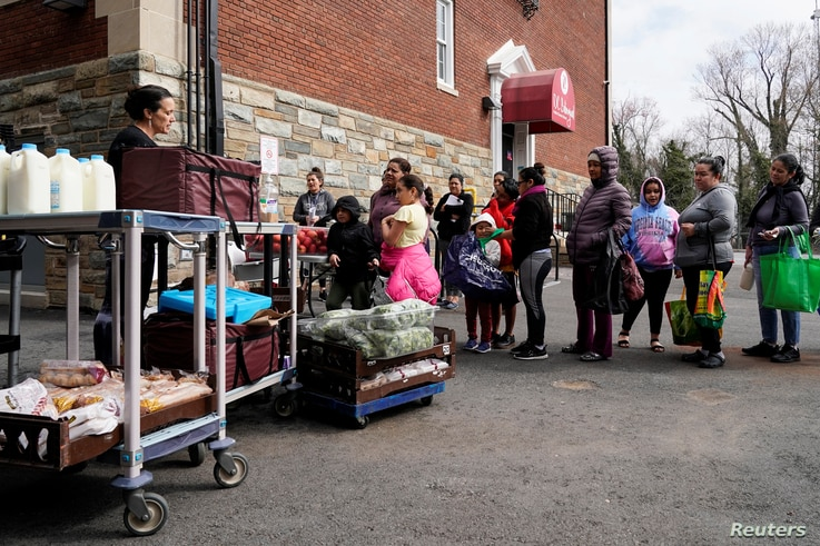 A member of staff gives food to families at the DC Bilingual School after the school was closed due to the global coronavirus pandemic in Washington, March 17, 2020.