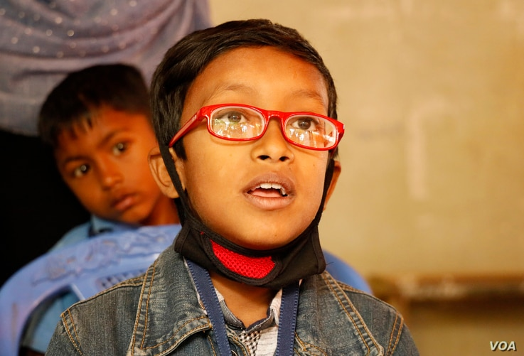 Ridowan from Kutupalong reads the eye chart with his first pair of glasses at the Kutupalong Government Primary School, Feb. 13, 2020.  (Hai Do/VOA)